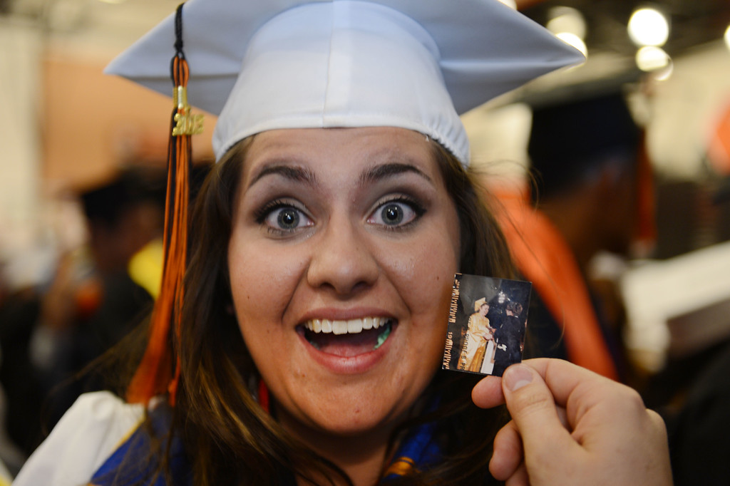 . Salutatorian Marisa Mota holds a 1994 Antioch High School graduation photo of her mom Christina Mota before the start of her 2013 commencement ceremony at Pittsburg High School in Pittsburg, Calif., Wednesday,  June 12, 2013. Mota wore the photo around her wrist as she gave her speech before her classmates.  (Susan Tripp Pollard/Bay Area News Group)
