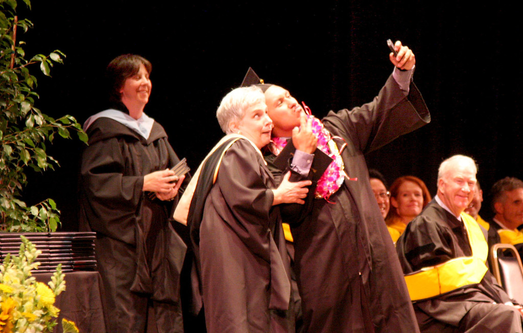 . Principal Pam Shay gets her photo snapped by Eric Hernandez on stage after he received his diploma at the 59th commencement ceremonies of Bishop O\'Dowd High School at the Paramount Theatre of the Arts in Oakland, Calif. on Sunday, June 2, 2013. (Jim Stevens/Bay Area News Group)