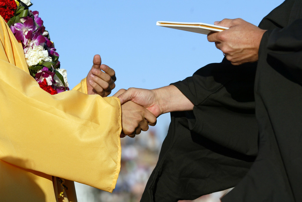 . A senior of the Class of 2013 recieves his diploma during the Alameda High School graduation ceremony at the College of Alameda soccer field in Alameda, Calif., on Friday, June 7, 2013.  (Ray Chavez / Bay Area News Group)