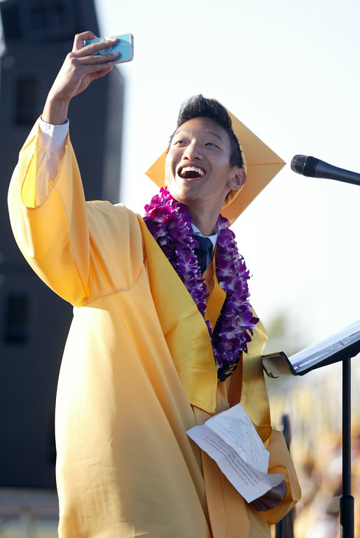 . Co-Salutatorian Jeremy Wan takes a picture of himself with his classmates seated in the background before speaking to the Class of 2013 and their family members, friends and faculty staff during the Alameda High School graduation ceremony at the College of Alameda soccer field in Alameda, Calif., on Friday, June 7, 2013.  (Ray Chavez / Bay Area News Group)