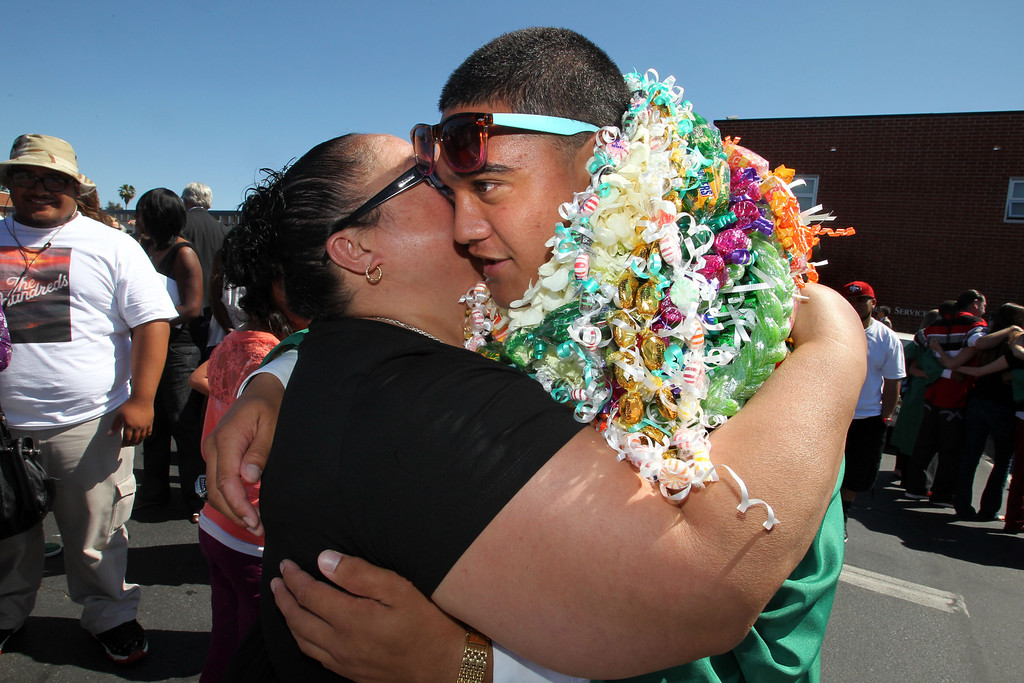 . Mui Vitale, left, embraces her son and De La Salle graduate Pepe Viatle following his commencement ceremony of the Class of 2013 at De La Salle High School in Concord , Calif., on Sunday, May 19, 2013. (Ray Chavez/Bay Area News Group)