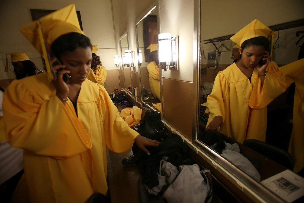 . Crystal Brooks makes a last-minute call as she gets ready to enter Oakland Technical High School graduation ceremonies at the Paramount Theatre in Oakland, Calif., on Tuesday, June 11,  2013. The school graduated 351 students in the class of 2013. (Jane Tyska/Bay Area News Group)