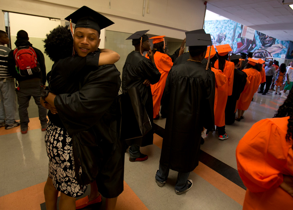 . Kenyatta Jackson, left, hugs his aunt, Brandi Mack, before entering the auditorium for graduation ceremonies for the Class of 2013 at McClymonds High School, Thursday, June 13, 2013 in Oakland, Calif. (D. Ross Cameron/Bay Area News Group)