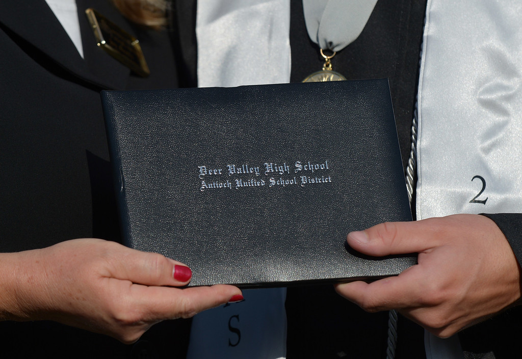 . Antioch Unified School District board member Joy Motts hands a diploma cover to valedictorian Alvin Vuong during graduation ceremonies at Deer Valley High School in Antioch, Calif., on Thursday, June 6, 2013. (Jose Carlos Fajardo/Bay Area News Group)