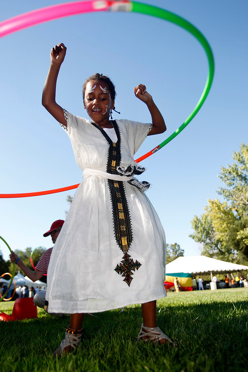 ". Margie Nielsen,7, of Salt Lake City, wears a traditional dress as she plays with hula hoop at the Ethiopian ""Enkutatash\"" new year celebration at Guadalupe River Park Arena Green West in downtown San Jose, Calif.,  on Sunday, Sept. 8, 2013. She has a twin sister and both where  adopted five years ago from Shashamane, Ethiopia. (Josie Lepe/Bay Area News Group)"
