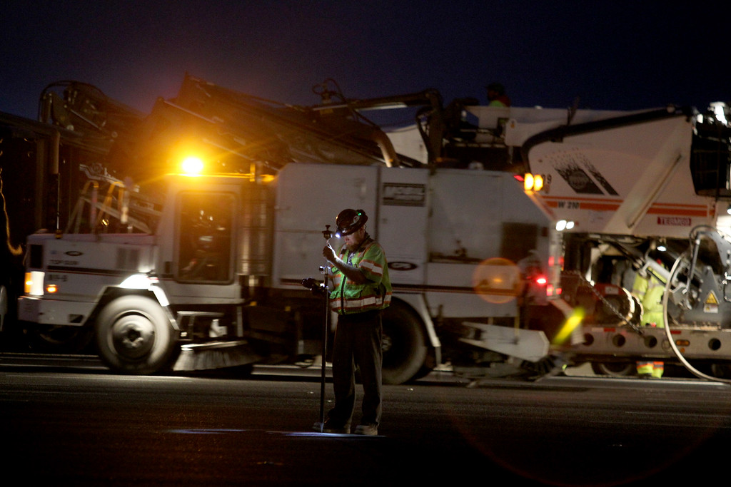 . Caltrans workers perform work near the toll plaza in Oakland, Calif., during the the Bay Bridge closure for the old and new eastern span on Wednesday, Aug. 28, 2013. The new eastern span is scheduled to open on Tuesday, Sept. 3, at 5 a.m. (Ray Chavez/Bay Area News Group)