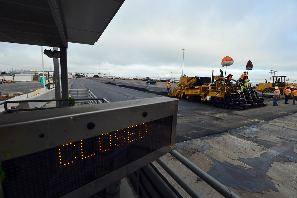 . Paving work is done on the toll booth approach to the Bay Bridge in Oakland, Calif. on Thursday, Aug. 29, 2013. (Kristopher Skinner/Bay Area News Group)