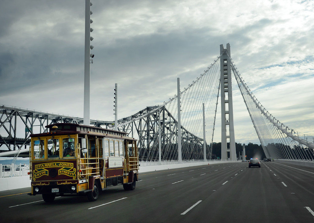 . No, they haven\'t added a cable car line to the new Bay Bridge. It is just one of the motorized cable cars used to carry guests of a bridge contractor party at the toll plaza late Sunday afternoon, Sept. 1, 2013, in Oakland, Calif. (Karl Mondon/Bay Area News Group)
