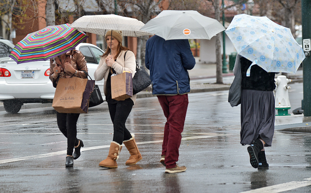 . Four people cross paths with umbrellas as they cross Main Street in Walnut Creek during a shower in Walnut Creek, Calif., on Friday, Feb. 28, 2014. (Dan Rosenstrauch/Bay Area News Group)