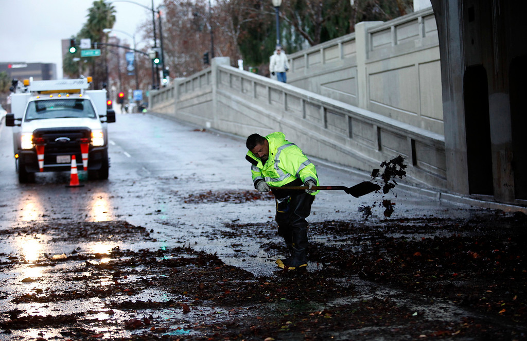 . City worker Gregory Dominguez cleans up an underpass on Santa Clara Street near Stockton Avenue that was flooded earlier in the morning in San Jose, Calif. on Friday, Feb. 28, 2014. Heavy rain prompted flooding and wind advisories in the Bay Area. (Gary Reyes/Bay Area News Group)