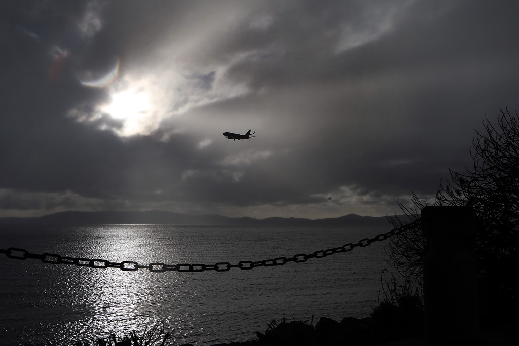 . An aircraft prepares to land at the Oakland International Airport in Oakland, Calif., as the sun breaks through the cloudy sky during a storm on Friday, Feb. 28, 2014. (Ray Chavez/Bay Area News Group)