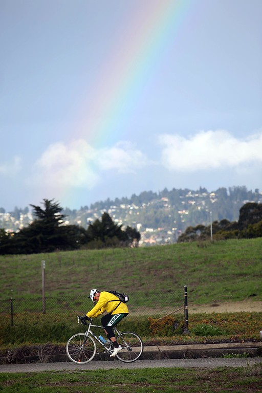 . A cyclist passes a rainbow as it appears over the East Bay hills in this view from along West Frontage Road in Emeryville, Calif., on Friday, Feb. 27, 2014. More showers are expected on Saturday according to the National Weather Service. (Jane Tyska/Bay Area News Group)