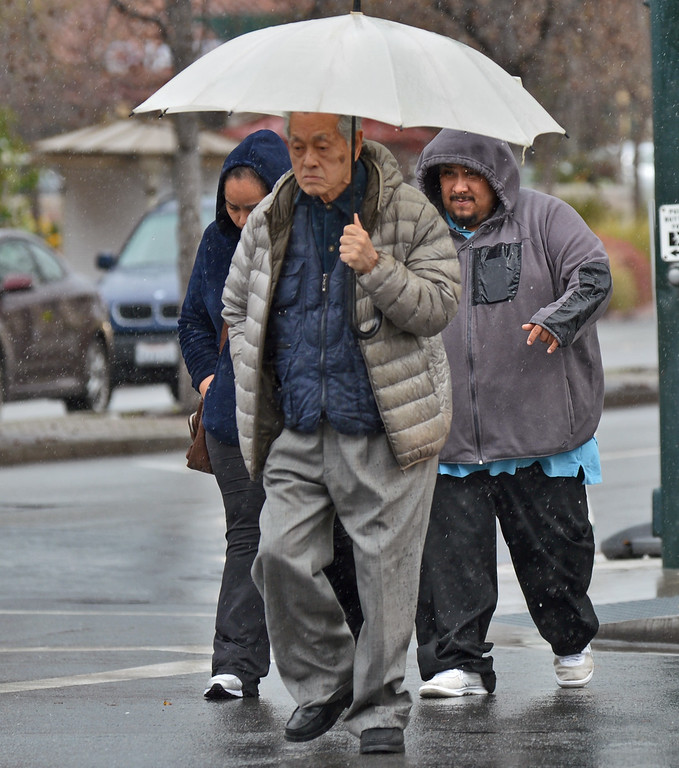 . A group of people hurry  as they cross Main Street in Walnut Creek during a downpour in Walnut Creek, Calif., on Friday, Feb. 28, 2014. (Dan Rosenstrauch/Bay Area News Group)