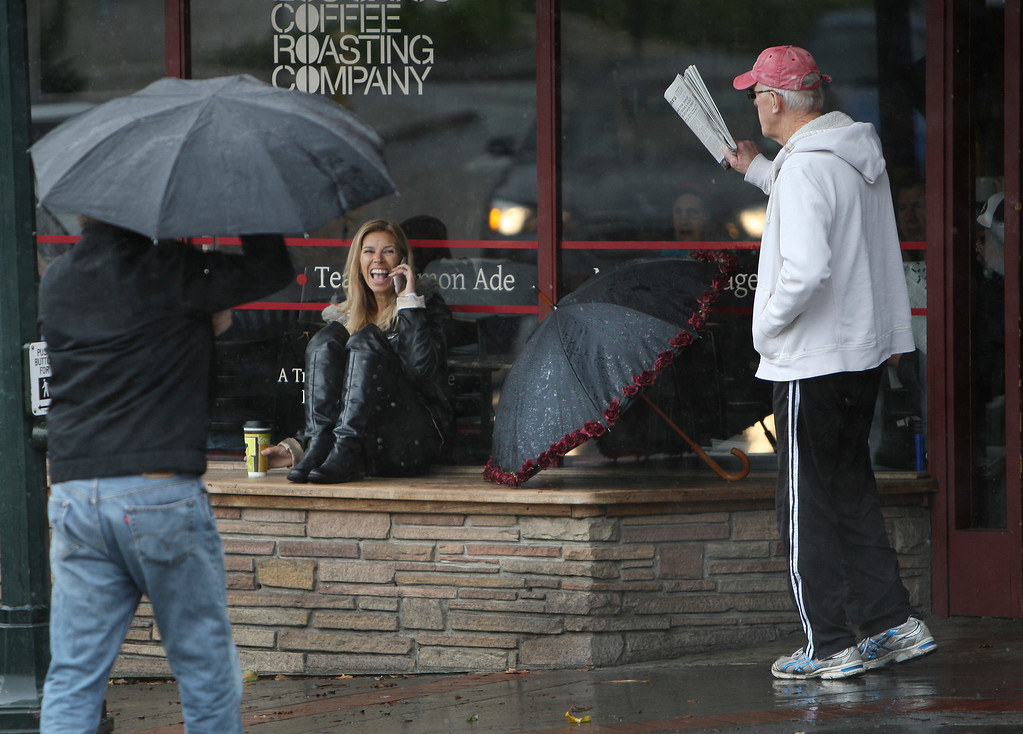 . Lisa Perry, of Los Gatos, chats on the phone in the rain as Larry Edgar, right, also of Los Gatos comes out of Los Gatos Coffee Roasting Company in Los Gatos, Calif. on Friday, Feb. 28, 2014. (Jim Gensheimer/Bay Area News Group)
