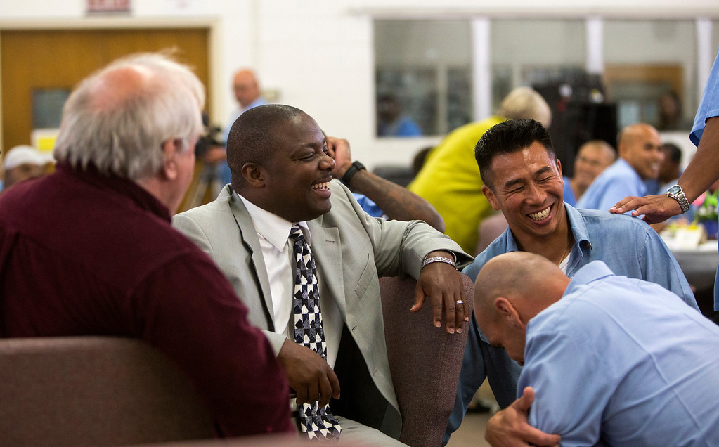 """. Lt. Sam Robinson, second from left, and Kid CAT member Nghiep \""""Ke\"""" Lam, back right, share a laugh at Kid CAT\'s curriculum launch. Each of the prison\'s 14 ILTAGs, or Inmate Leisure Time Activity Groups, must be overseen by a member of the prison staff. Robinson is Kid CAT\'s chief sponsor. (John Green/Bay Area News Group)"""