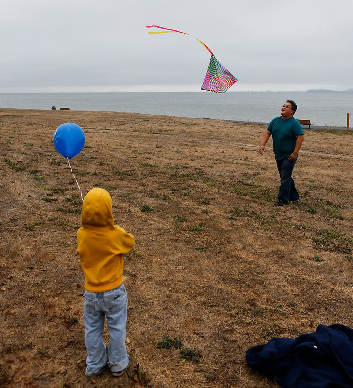 . Sondi Tran helps son Dylan, 4, fly a kite at Oyster Point Marina and Park in South San Francisco, Calif., on Saturday, Sept. 14,  2013. The San Mateo County Harbor District held a kite festival on Saturday as part of their 80th anniversary celebration. (John Green/Bay Area News Group)