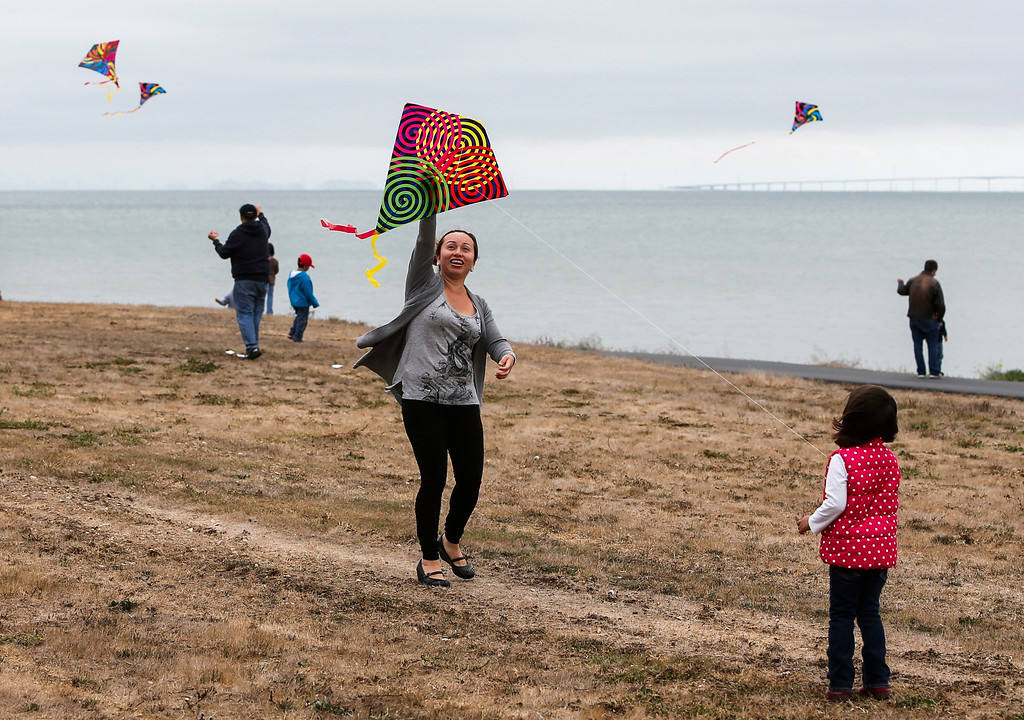 . Karina Perez, middle, helps daughter Abril, 4, fly her kite at Oyster Point Marina and Park in South San Francisco, Calif., on Saturday, Sept. 14,  2013. The San Mateo County Harbor District held a kite festival on Saturday as part of their 80th anniversary celebration. (John Green/Bay Area News Group)