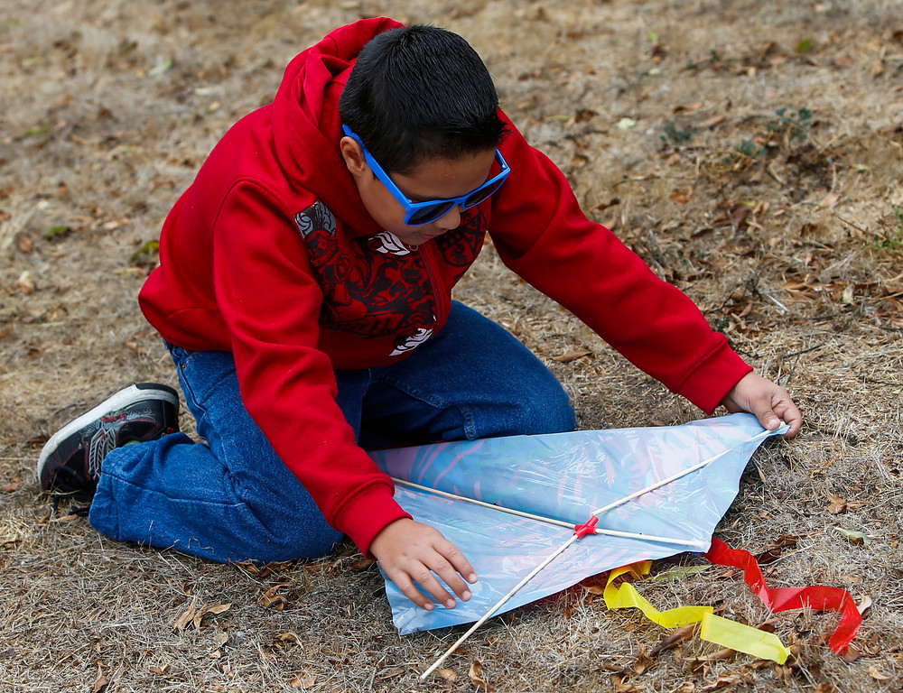 . Jose Soto, 10, puts his kite together at Oyster Point Marina and Park in South San Francisco, Calif., on Saturday, Sept. 14,  2013. The San Mateo County Harbor District held a kite festival on Saturday as part of their 80th anniversary celebration. (John Green/Bay Area News Group)