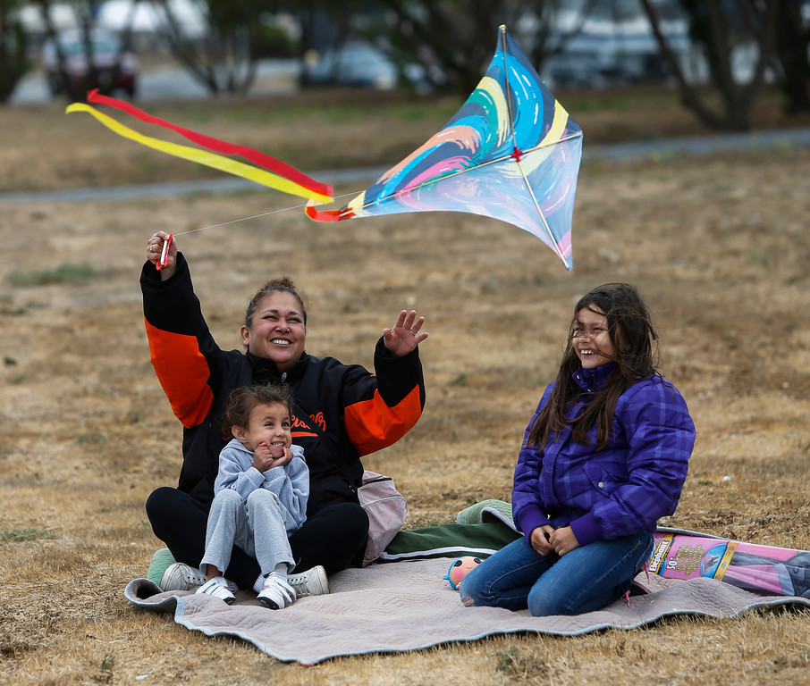 . Adrienne Williams, of South San Francisco, helps daughters, from left, Aurora Scripps, 5, and Michaela Scripps, 8, fly a kite at Oyster Point Marina and Park in South San Francisco, Calif., on Saturday, Sept. 14,  2013. The San Mateo County Harbor District held a kite festival on Saturday as part of their 80th anniversary celebration. (John Green/Bay Area News Group)