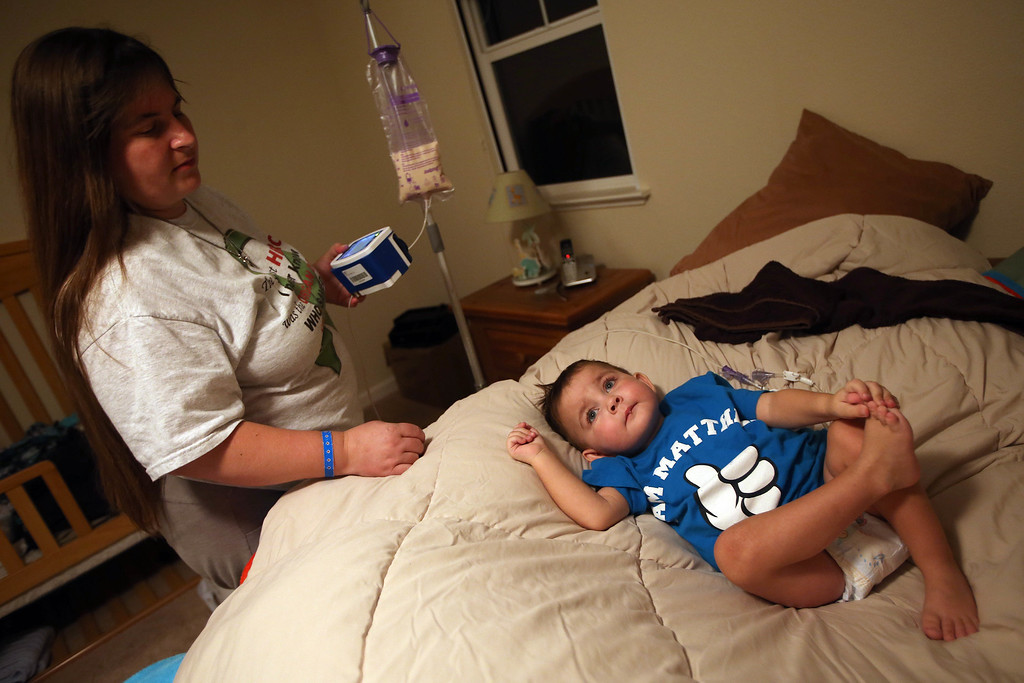. Kristi Ouimet, of Antioch, left, sets up her son Matthew\'s feeding formula as she puts him to bed at the Ouimet\'s home in Antioch, Calif., on Wednesday, Aug. 14, 2013. Matthew, 2, was discharged from the UCSF Benioff Children\'s Hospital in San Francisco Wednesday after spending 73 days there recovering from a liver/kidney transplant on June 4. It was Kristi\'s first time home since then. (Jane Tyska/Bay Area News Group)