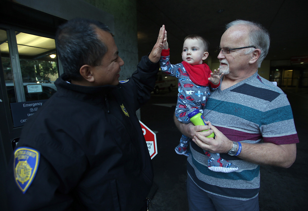 """. Security guard Mel Velasco, left, gives a high five to Matthew Ouimet, 23 months, of Antioch, at UCSF Benioff Children\'s Hospital in San Francisco, Calif., on Tuesday, Jan. 22, 2013. To the right is Matthew\'s grandfather Jim Wisecarver, also of Antioch.\""""He\'s my inspiration,\"""" Velasco said. \""""I always pray for my buddy.\"""" Matthew is still awaiting both a liver and kidney transplant and does hemodialysis at UCSF Medical Center six times per week. (Jane Tyska/Staff)"""