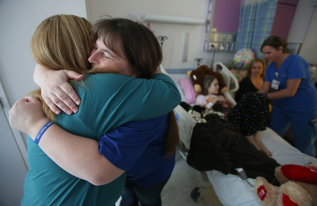 . Kristi Ouimet, of Antioch, right, gets a hug from friend Kim Welch, of Riverbank, Calif., at UCSF Benioff Children\'s Hospital in San Francisco, Calif., on Tuesday, Jan. 22, 2013. Welch\'s daughter, Alyssa, 15, far right, received a liver and kidney transplant on Jan. 15 and is doing well after surgery. Ouimet\'s son Matthew, 23 months, is still awaiting both a liver and kidney transplant and does hemodialysis at UCSF Medical Center six times per week. (Jane Tyska/Staff)