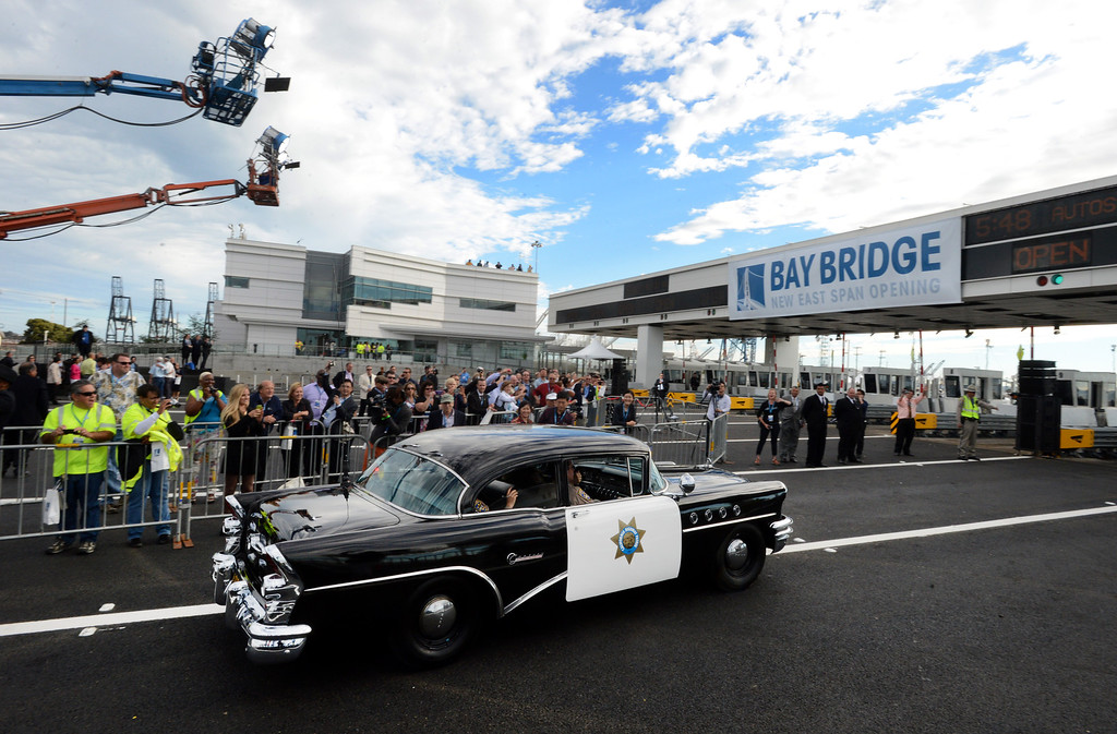 . An old California Highway Patrol drives towards the toll plaza as classic cars follow motorcycle CHP onto the new eastern span of the Bay Bridge in Oakland, Calif., on Monday, Sept. 2, 2013. The new 2.2 mile replacement eastern span with its skyward and iconic white tower and cables, is the world\'s largest self-anchored suspension span and California\'s most expensive infrastructure project to date. (Susan Tripp Pollard/Bay Area News Group)