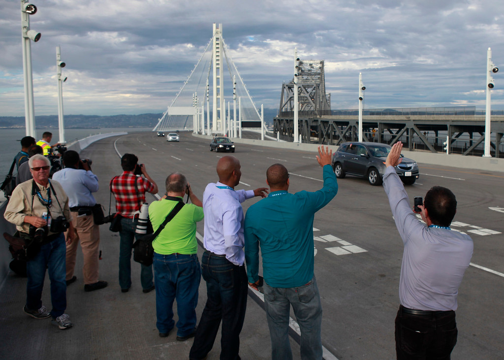 . Media and their handlers watch vintage vehicles drive in a procession over the new Bay Bridge after the traditional chain-cutting ceremony Monday afternoon Sept. 2, 2013  Oakland, Calif.   (Karl Mondon/Bay Area News Group)