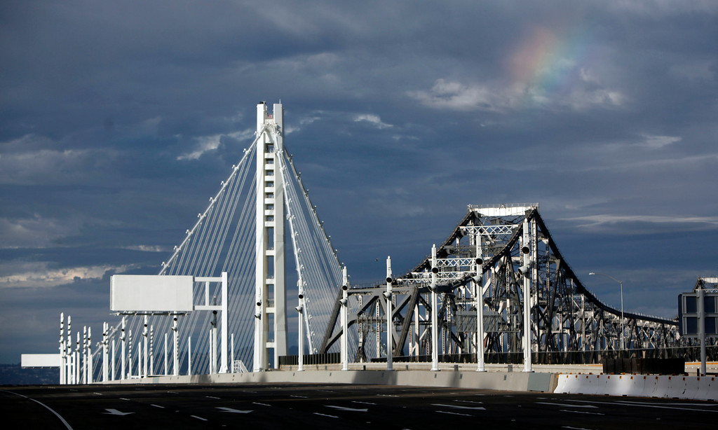 . A rainbow colors the sky over the new and old Bay Bridges after a traditional chain-cutting ceremony by Lt. Gov. Gavin Newsom marked the opening of the span  Monday afternoon Sept. 2, 2013 in Oakland, Calif. (Karl Mondon/Bay Area News Group)