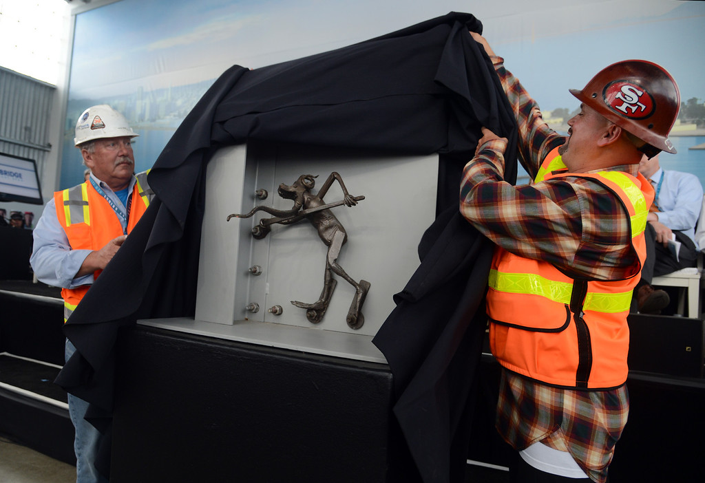 . Jerry Kent and Scott Smith unveil the mysterious Bay Bridge troll after a two hour grand opening ceremony for the new Bay Bridge Monday afternoon Sept. 2, 2013 in Oakland, Calif. The troll had disappeared from its spot on the old Bay Bridge where it had guarded the span against further harm for the past 24 years since the Loma Prieta Earthquake. (Karl Mondon/Bay Area News Group)