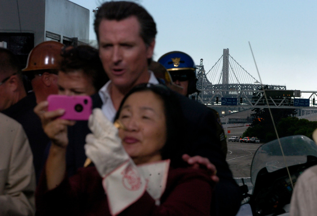 . The single tower of the new Bay Bridge rises in the distance as California Lt. Governor Gavin Newsom and Oakland Mayor Jean Quan take a picture together during a chain-cutting ceremony to celebrate the completion of the new Bay Bridge in Oakland, Calif., on Monday, Sept. 2, 2013. (Kristopher Skinner/Bay Area News Group)