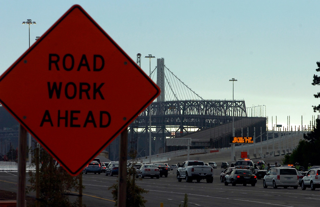 . A line of cars in a ceremonial procession heads up the incline onto the new span of the Bay Bridge following a chain-cutting ceremony in Oakland, Calif., on Monday, Sept. 2, 2013. (Kristopher Skinner/Bay Area News Group)