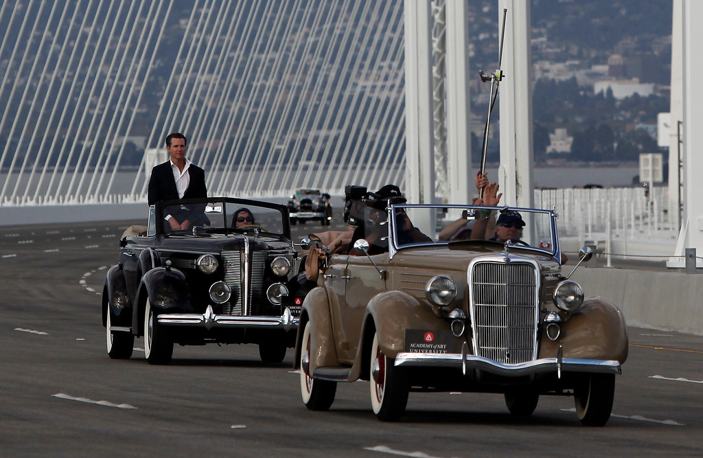 . Lt. Gov. Gavin Newsom rides in a vintage vehicle over the new Bay Bridge after cutting the chain in a traditional bridge-opening ceremony Monday afternoon, Sept. 2, 2013  Oakland, Calif.   (Karl Mondon/Bay Area News Group)