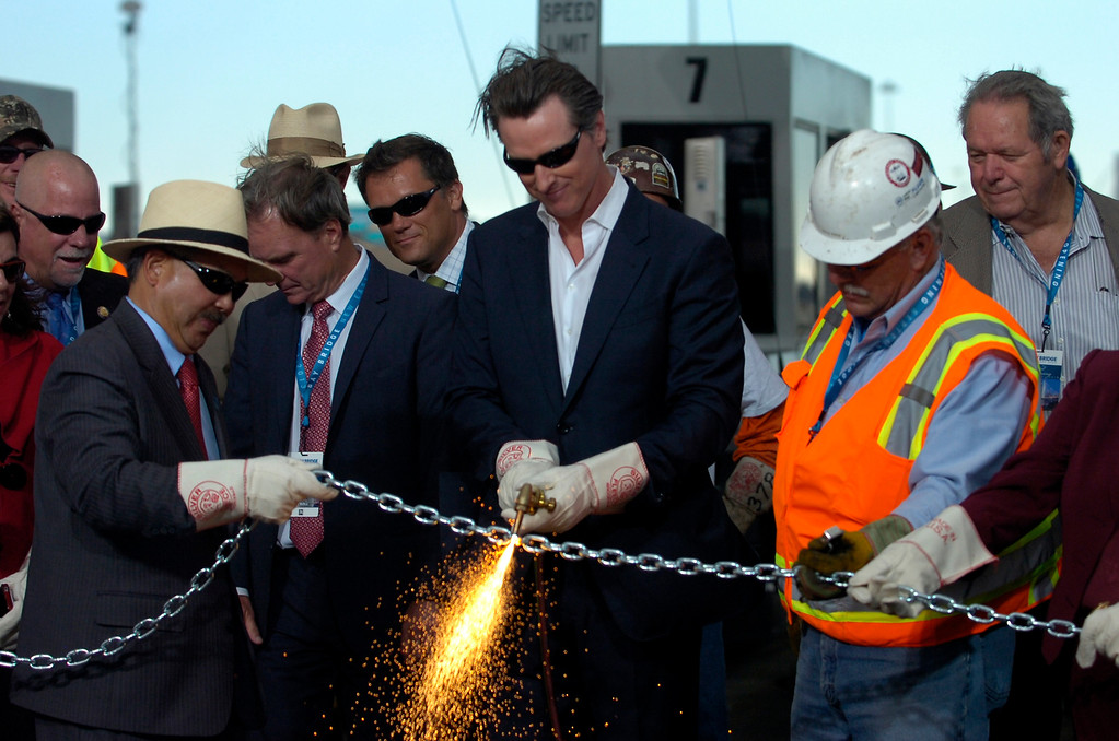 . California Lt. Governor Gavin Newsom uses a cutting torch during a chain-cutting ceremony to celebrate the completion of the new Bay Bridge in Oakland, Calif., on Monday, Sept. 2, 2013. (Kristopher Skinner/Bay Area News Group)