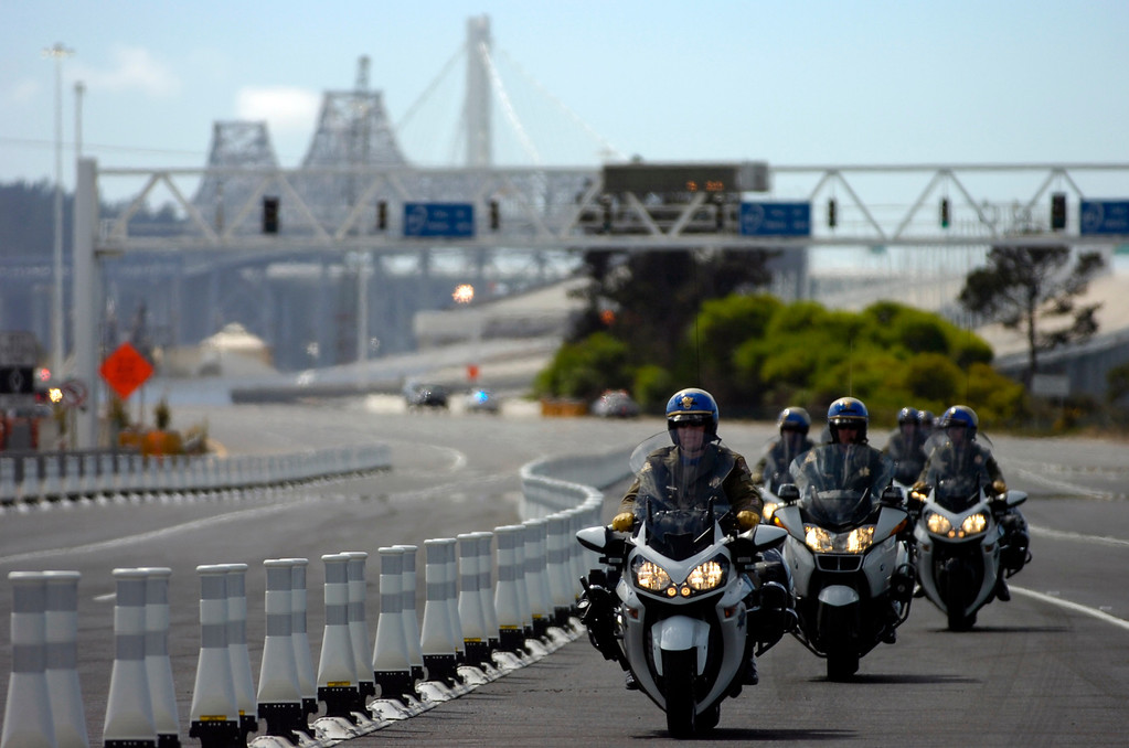 . Motorcycle police officers ride toward the Bay Bridge toll plaza prior to a chain-cutting ceremony to celebrate the completion of the new Bay Bridge in Oakland, Calif., on Monday, Sept. 2, 2013. (Kristopher Skinner/Bay Area News Group)