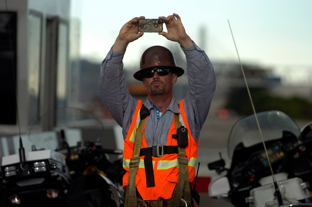 . A worker takes a picture during a chain-cutting ceremony to celebrate the completion of the new Bay Bridge in Oakland, Calif., on Monday, Sept. 2, 2013. (Kristopher Skinner/Bay Area News Group)