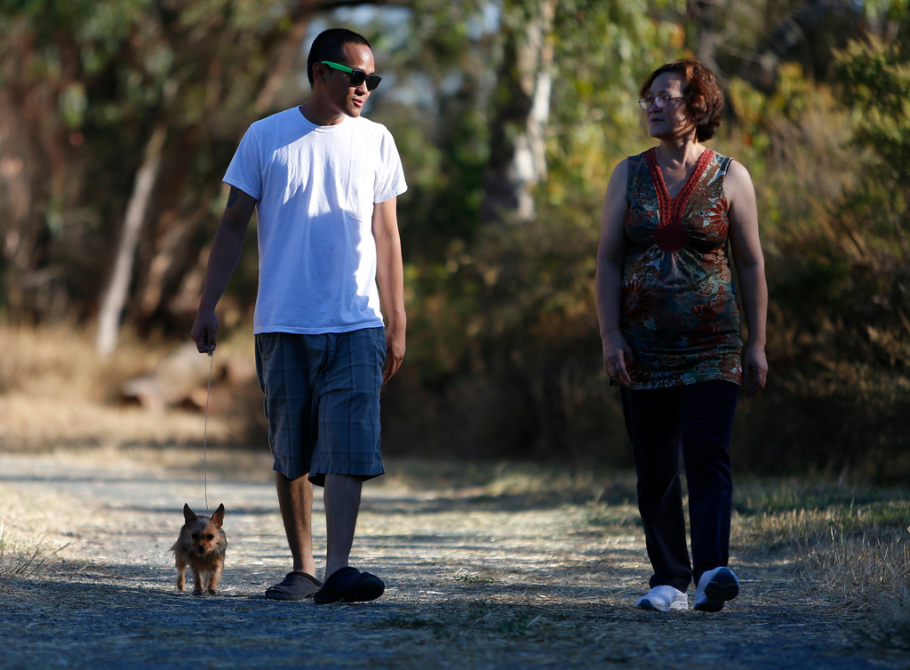 . Joselito Natnat, left, walks his dog Snicky, along with his mom Olivia Natnat, all from Santa Clara, at Ulistac Natural Area in Santa Clara, Calif. on Thursday, Sept. 19, 2013.  The 49ers and the city of Santa Clara are proposing to develop part of a 40-acre natural open space into soccer fields to make way for extra parking next to the new stadium.  Joselito was sad to hear that they might replace parts of the area with a soccer field, he likes to have the natural space to close by.  (Nhat V. Meyer/Bay Area News Group)