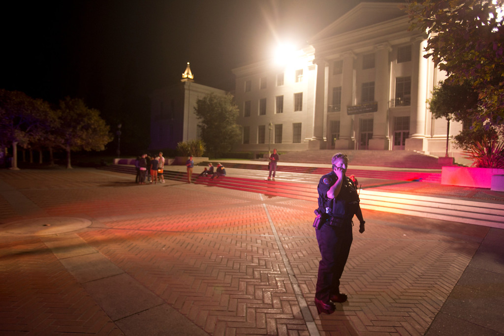 . A University of California police officer, right, guards the entrance to a darkened Sproul Plaza after an explosion and fire in an underground utility vault caused a power outage and forced the evacuation of the campus, Monday, Sept. 30, 2013 in Berkeley, Calif. (D. Ross Cameron/Bay Area News Group)