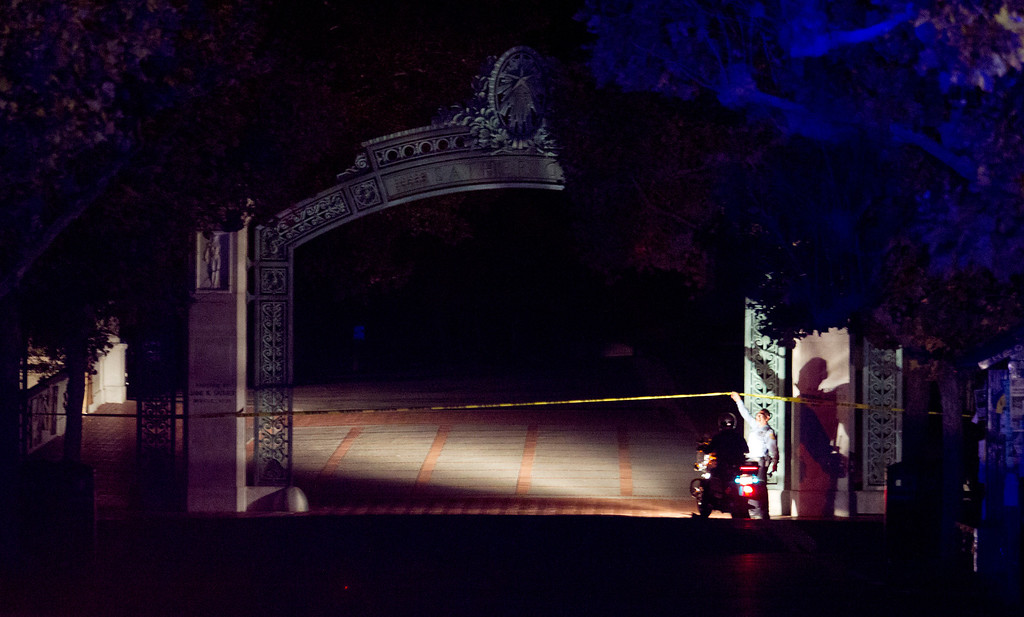 . A University of California police officer lifts the crime scene tape so another officer can get through Sather Gate after an explosion and fire in an underground utility vault caused a power outage and forced the evacuation of the campus, Monday, Sept. 30, 2013 in Berkeley, Calif. (D. Ross Cameron/Bay Area News Group)