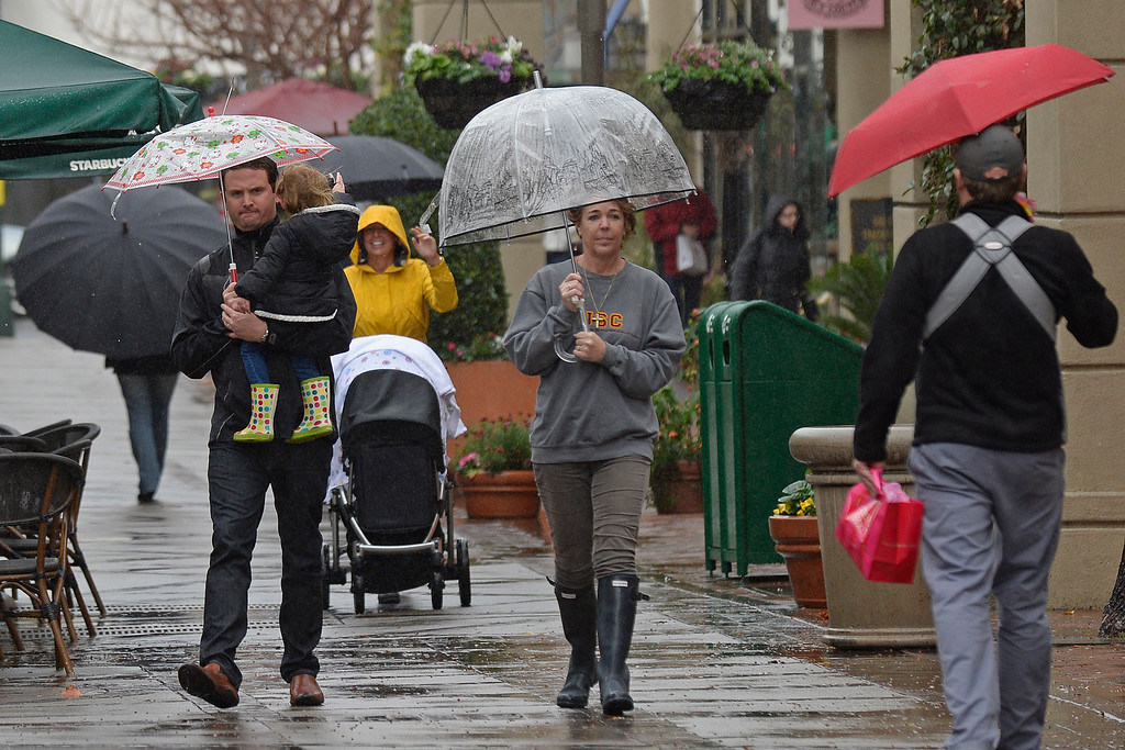 . Shoppers carry umbrellas as clouds bring rain to  Broadway Plaza in Walnut Creek, Calif., on Saturday, Feb. 8, 2014. (Jose Carlos Fajardo/Bay Area News Group)