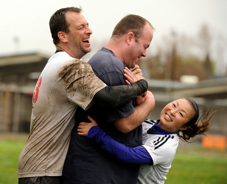 . At the end of their Ultimate Frisbee game two members of the white team, Tim Culler of Walnut Creek, left, and Marie Kokawa of Concord give a big wet mud slimy hug to a fairly clean and dry Brian King of Pleasant Hill, a member of the team wearing color shirts in Pleasant Hill, Calif., Sunday, Feb. 9, 2014. The wet weather did not bother the players who slipped and slid on the field and cleaned up in nearby puddles after their game. (Susan Tripp Pollard/Bay Area News Group)