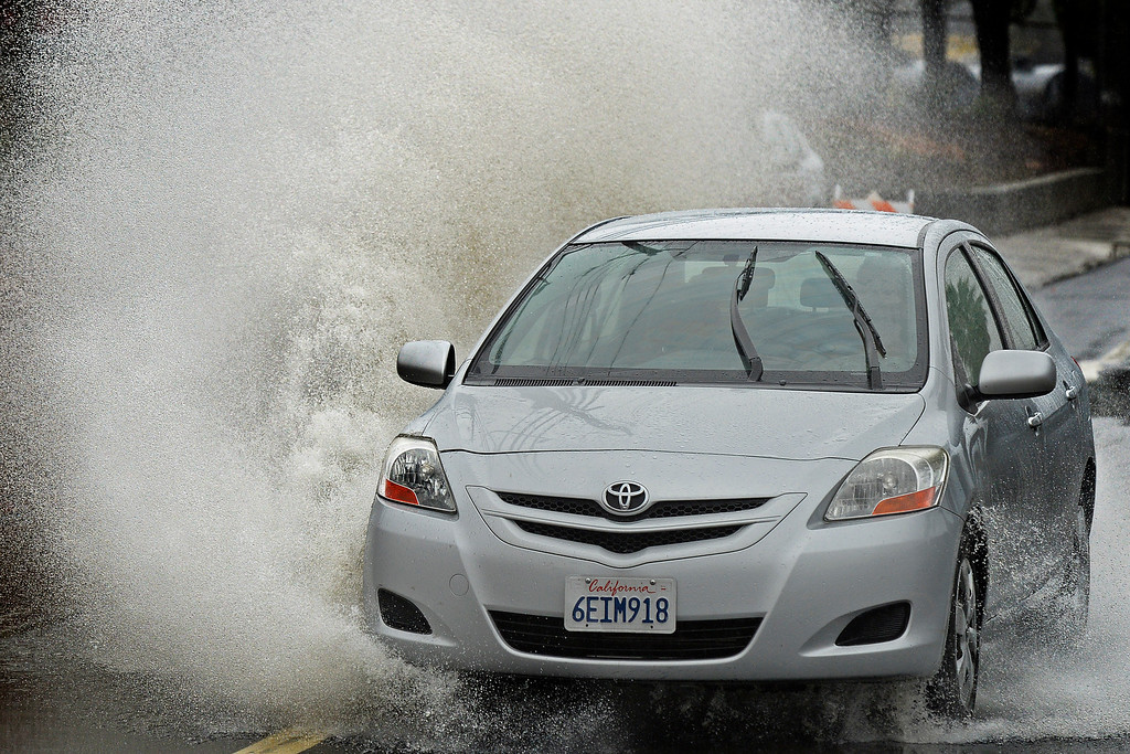 . A vehicle drives through a flooded street caused by a blocked storm drain on Marina Vista Ave. in Martinez, Calif., on Saturday, Feb. 8, 2014. (Jose Carlos Fajardo/Bay Area News Group)