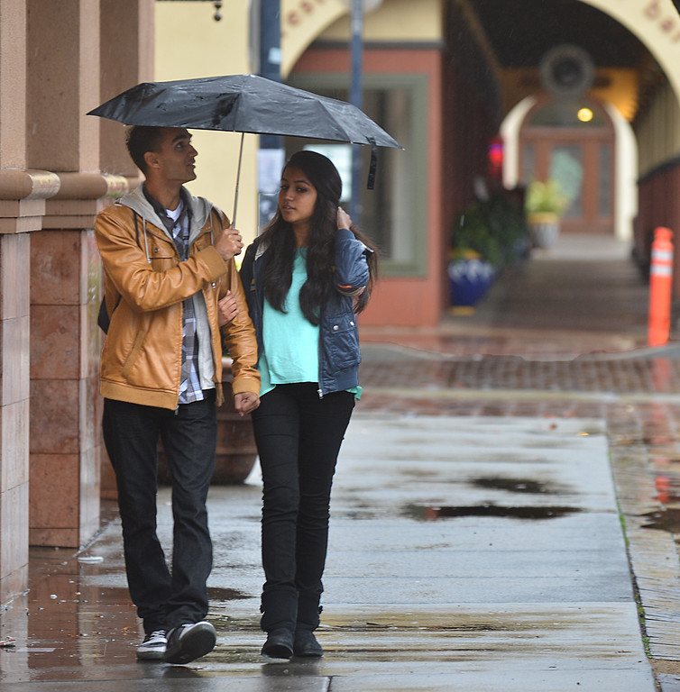 . Joshua Davidson, left, and Abigail Alfred, right, both from Pleasant Hill, hold an umbrella over their heads in the rain as they walk down Salvio Street in Concord, Calif., on Saturday, Feb. 8, 2014. (Dan Rosenstrauch/Bay Area News Group)