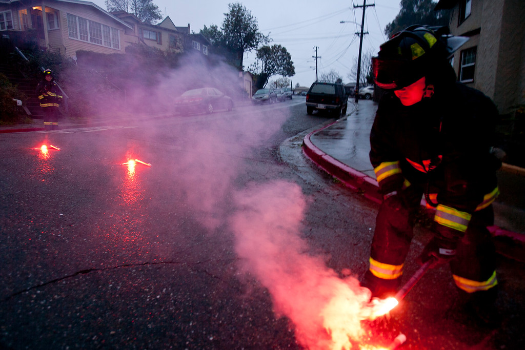 . An Oakland firefighter places traffic flares at the intersection of Redding Street and Storer Avenue in Oakland, Calif., on Sunday, Feb. 9, 2014, after heavy rain caused power lines to arc and threaten to ignite utility poles in the area. (D. Ross Cameron/Bay Area News Group)