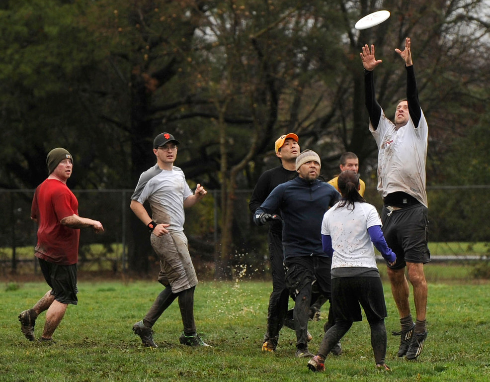 . Tim Culler, of Walnut Creek, a member of the white team goes up for a pass during an Ultimate Frisbee game held in Pleasant Hill, Calif., Sunday, Feb. 9, 2014. The wet weather did not bother the players who slipped and slid on the field and cleaned up in nearby puddles after their game. (Susan Tripp Pollard/Bay Area News Group)