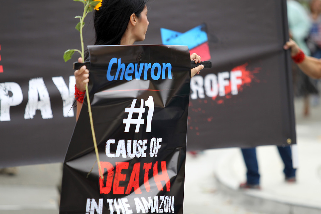 . A demonstrator holds a sign as he marches to the Chevron refinery after a rally at Richmond BART station in Richmond, Calif., on Saturday, Aug. 3, 2013.  (Ray Chavez/Bay Area News Group)