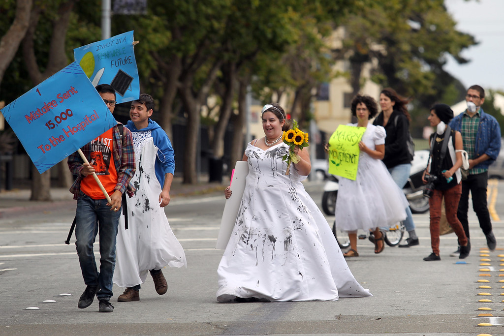 . Caleb Feldman, second from left, Katie Loncke and Dawn Haney, back, of Oakland, march to the Chevron refinery after a rally at Richmond BART station in Richmond, Calif., on Saturday, Aug. 3, 2013. (Ray Chavez/Bay Area News Group)