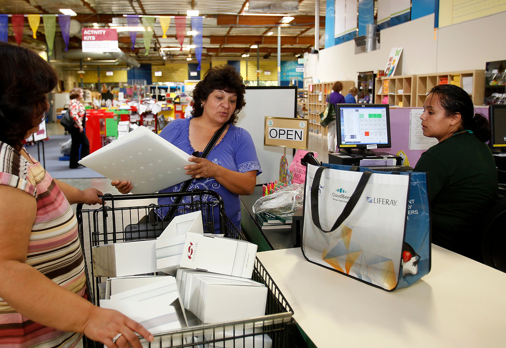 . San Jose Unified second grade teacher Gracie Cortez, center, unpacks a cart at the check-out buying supplies -- a Thesaurus, boxes for level reading books -- to be rung up by cashier Martha Alvarado, right, at Resource Area For Teaching in San Jose, Calif., on Saturday, Aug. 10, 2013. (Josie Lepe/Bay Area News Group)