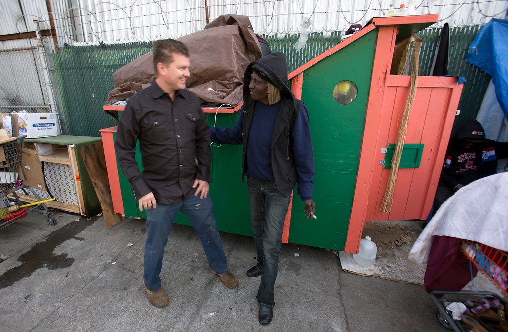 """. Greg Kloehn, who takes discarded trash and turns it into rolling shelters for homeless people in his west Oakland, Calif. neighborhood, greets \""""Wonder,\"""" a homeless woman who now lives in the shelter he built for her, Tuesday, Dec. 31, 2013. (D. Ross Cameron/Bay Area News Group)"""