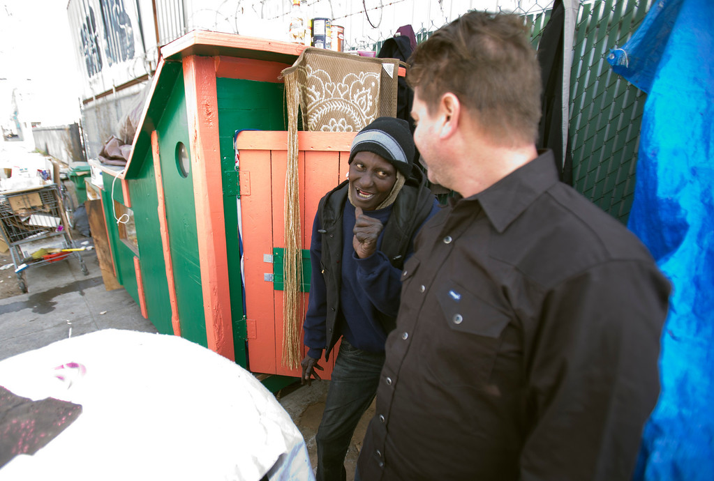 """. Greg Kloehn, right, who takes discarded trash and turns it into rolling shelters for homeless people in his west Oakland, Calif. neighborhood, greets \""""Wonder,\"""" a homeless woman who now lives in the shelter he built for her, Tuesday, Dec. 31, 2013. (D. Ross Cameron/Bay Area News Group)"""